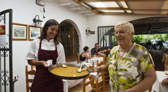 Rosa Devesa, a la derecha, sostiene un plato de arroz junto a su nieta Diana en su restaurante de Dénia.