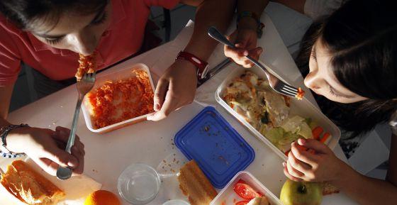 Dos niñas en edad escolar comen comida preparada en casa.