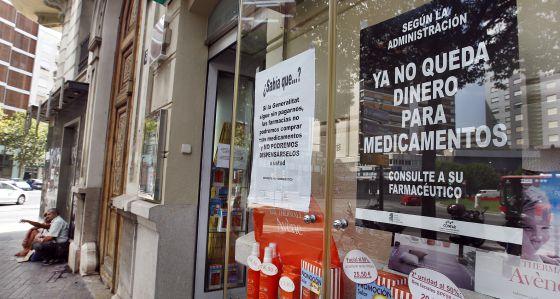Escarapate de una farmacia en el centro de la ciudad de Valencia en el que se muestra un cartel contra los impagos