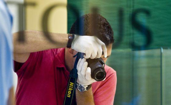 Un agente toma fotografías del interior de la joyería Tous del paseo de Gràcia tras ser atracada