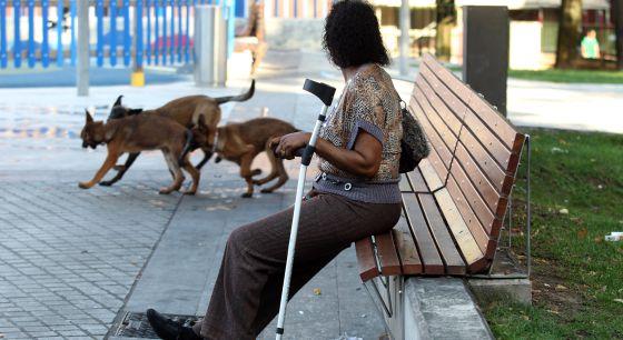 Mónica, una inmigrante guineana sin papeles, sentada en un banco en una calle de Bilbao.