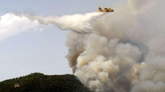 Un avión suelta agua sobre el incendio de Torremanzanas.