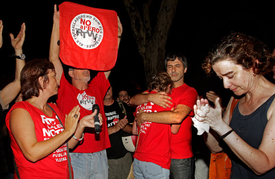 Trabajadores afectados por el ERE se abrazan a las puertas de la sede del consejo de administración de RTVV, de madrugada.
