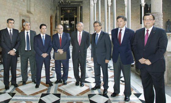 De izquierda a derecha, Xavier Adserà; el secretario del Gobierno catalán, Germà Gordó; Enrique Bañuelos; Andreu Mas-Colell; el presidente de La Caixa, Isidre Fainé; Artur Mas; Lluís Recoder, y Francesc Xavier Mena.