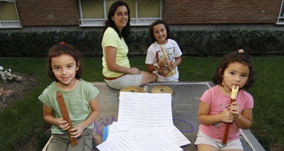 Estíbaliz Garrido y sus tres hijas, junto a su casa de Vallecas. Las dos mayores y ella misma son alumnas de una escuela municipal de música.