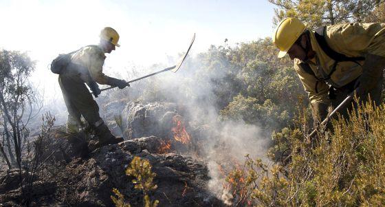 Dos brigadistas trabajan en la extinción del incendio de Benicolet.