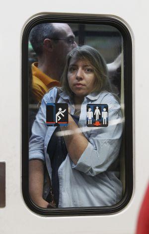 Mujer tras la puerta de un vagón abarrotado.