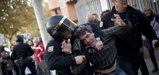 Javier Antona es reducido por un agente de policía.