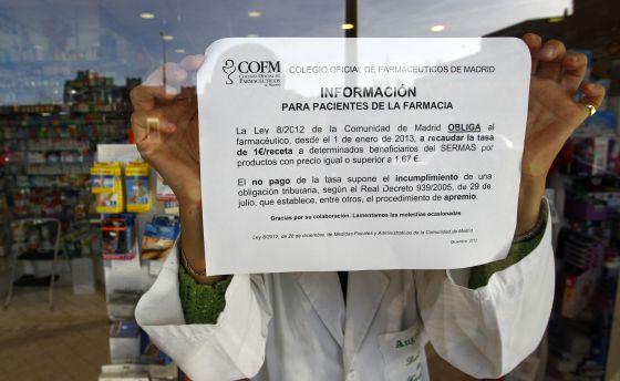 Cartel donde se explica el cobro de euro por receta en una farmacia de Madrid.