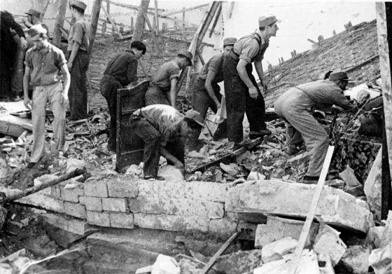 Ciudadanos y combatientes republicanos salvan pertenencias tras un bombardeo aéreo en el grupo de Casas Baratas de Sant Adrià del Besòs (Barcelona).