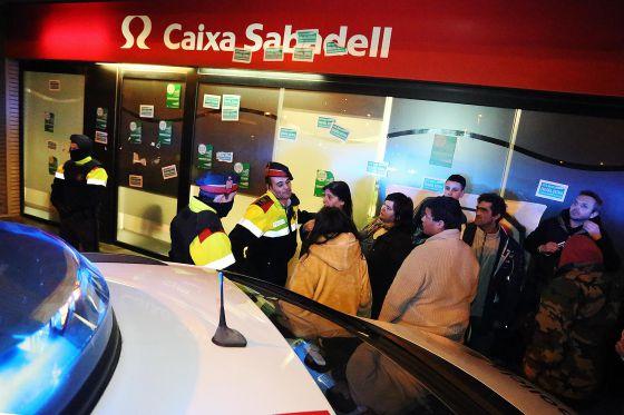 Los mossos desalojan una oficina bancaria ocupada por la pah for Oficinas bancarias abiertas por la tarde