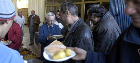 Un voluntario reparte comida a varios hombres en el Banco de Alimentos de Jaén.