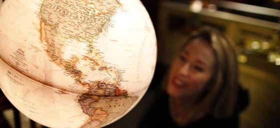 Una mujer ante un globo terráqueo en el espacio National Geographic.