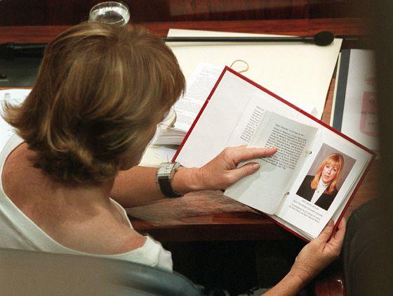 Esperanza Aguirre consulta en el libro de diputados de la Asamblea de Madrid la ficha de María Teresa Sáez, el 10 de junio de 2003.