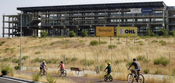 Cyclists make their way past the unfinished aquatic center, which was set to be a key venue had Madrid's Olympic bid prospered.