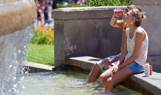 Dos jóvenes se refrescan en la plaza de Catalunya de Barcelona.