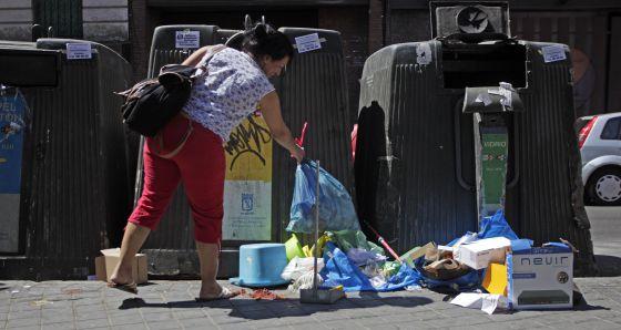 Una mujer deja una bolsa de basura en el suelo en Madrid.