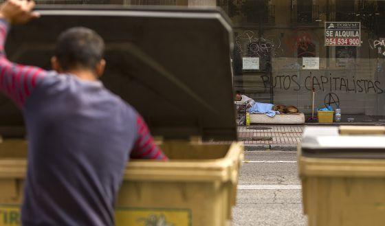 Un hombre busca en la basura delante de un mendigo que vive en la calle.