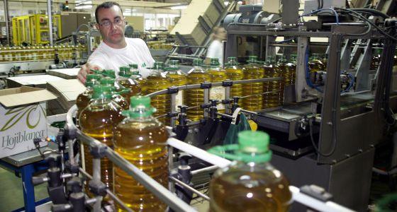 Un empleado supervisa la cadena de envasado de aceite de oliva.