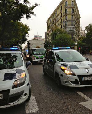 Vehículos de la policía municipal escoltan furgonetas de servicios mínimos de limpieza por el centro de Madrid.