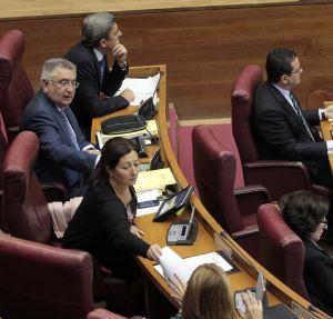 La diputada Maritina Hernández (izquierda) pasa a Trinidad Miró el escrito de apoyo al exalcalde de Torrevieja, mientras su compañero Fernando Giner contempla la escena desde su escaño.