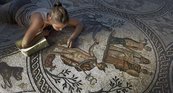 Una restauradora trabaja en el mosaico de los amores, en el yacimiento de Cástulo.