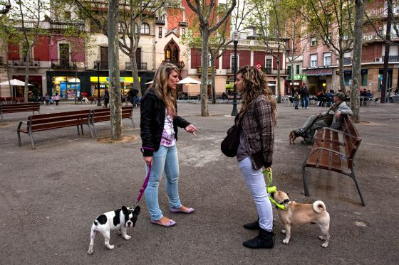 Two young people walk their dogs in Barcelona's Horta neighborhood.