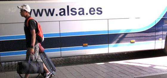Un joven marcha con equipaje junto a un autobús de Alsa.