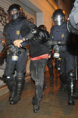 Dos agentes practicando una de las detenciones tras los disturbios.