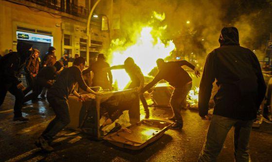 Manifestantes queman contenedores en el barrio de Sants.