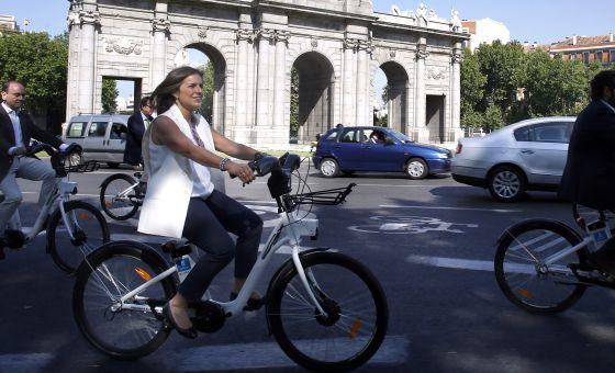 Ana Botella pasea en bicicleta por la Puerta de Alcalá.