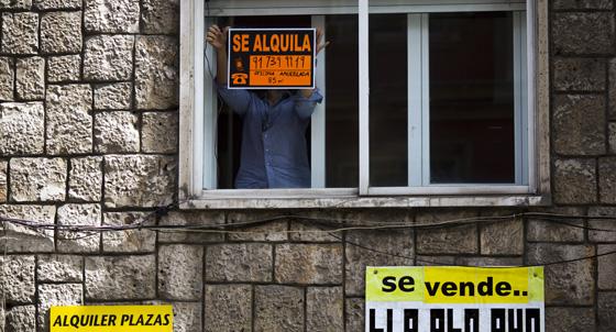 Un hombre coloca un cartel de alquiler en una vivienda de Madrid.