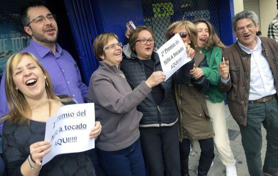 Varios de los afortunados con el primer premio de la lotería del Niño frente a la administración número tres de La Vall d'Uixò.