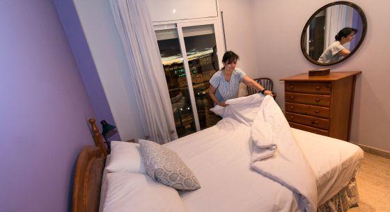 Una camarera de piso limpia una habitación y prepara la cama