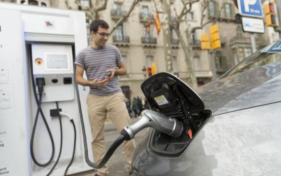 Un conductor enchufa su coche eléctrico en un punto de recarga rápida ubicado en el paseo de Gràcia.