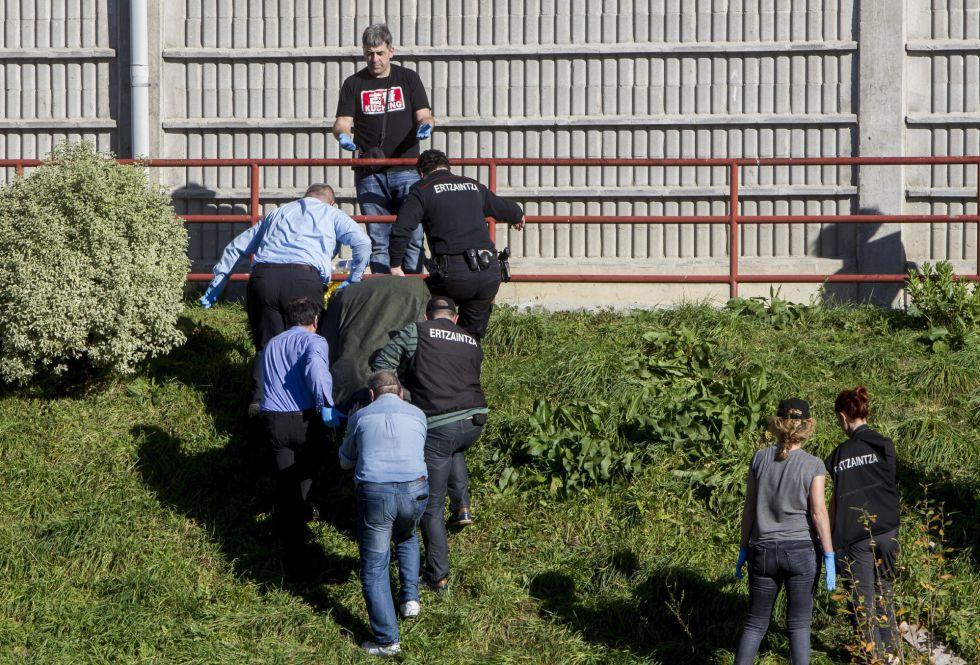 Personal de la funeraria y agentes de la Ertzaintza trasladan el cuerpo sin vida de una mujer fallecida este domingo en Bilbao.