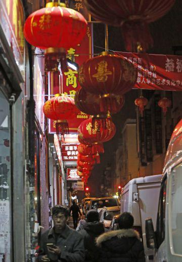 Vecinos caminan bajo los farolillos que anuncian el año nuevo chino.