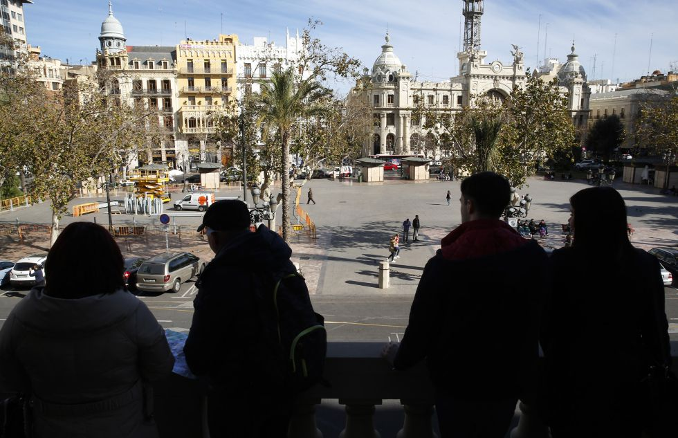 Turista en el balcón del Ayuntamiento miran los trabajos de montaje del dispositivo para las 'mascletades'.