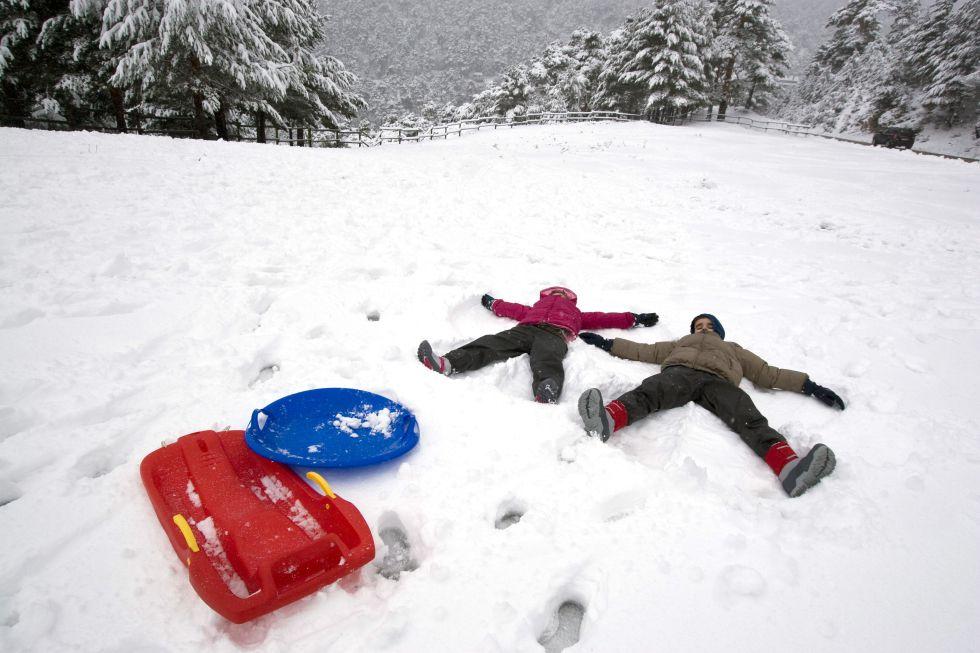 Dos niños disfrutan de la primera nevada de la temporada en el puerto de Navacerrada.