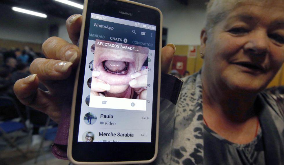 Josefa García muestra una fotografía de su boca sin dientes tras el cierre de Funnydent.