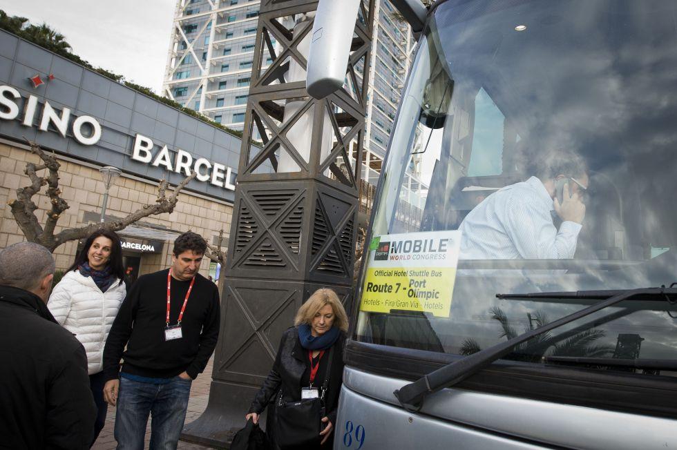 Congresistas del Mobile suben a un autobús para ir al recinto ferial.