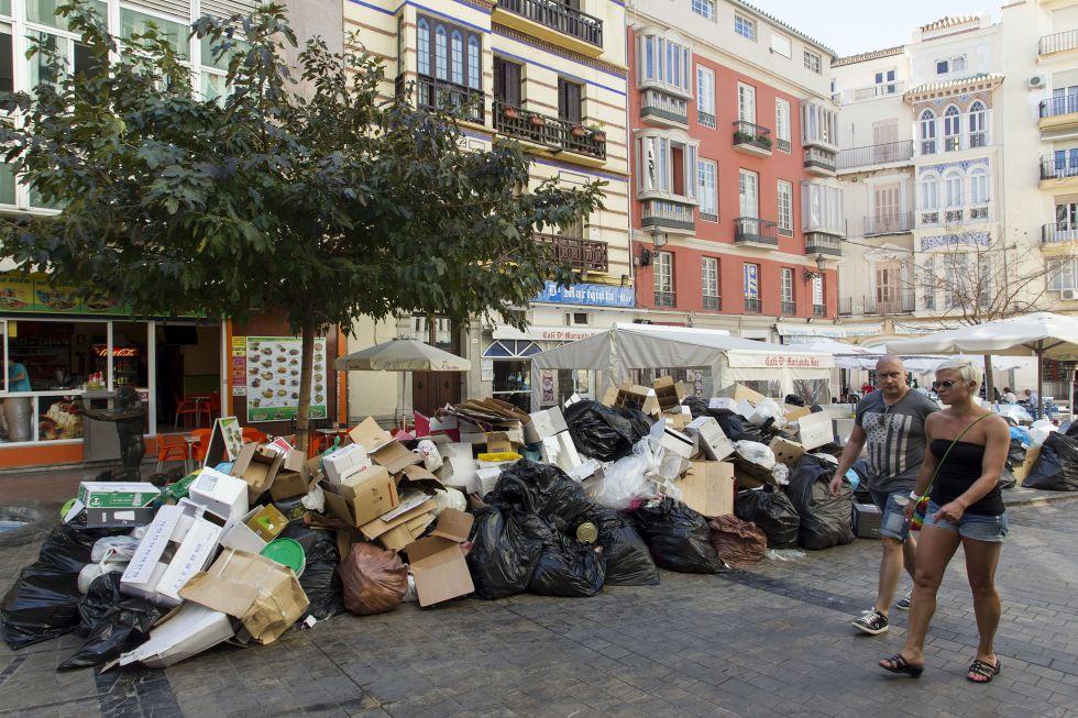 Unas personas pasan frente a basura acumulada en el centro de Málaga.