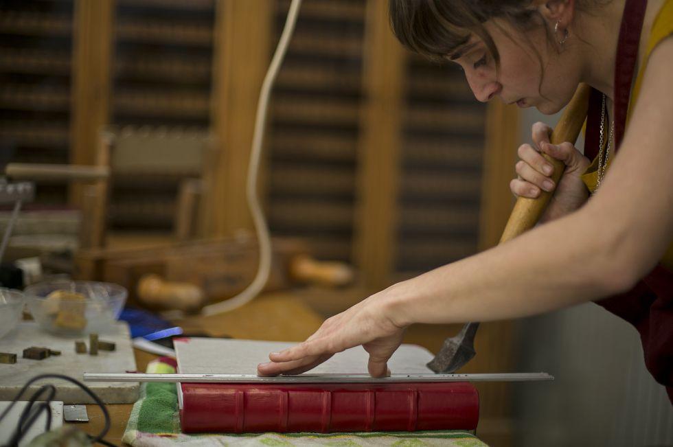 Una alumna encuadernando un libro en la Escuela de Diseño y Arte de la Llotja.