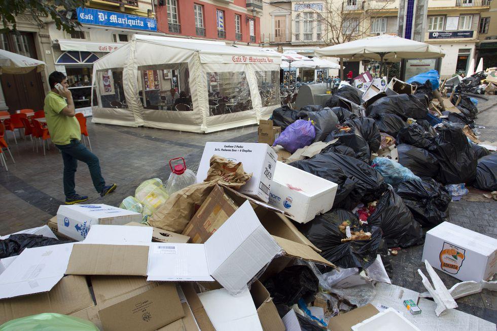 Un vecino pasa junto a la basura acumulada en una plaza del centro de Málaga.