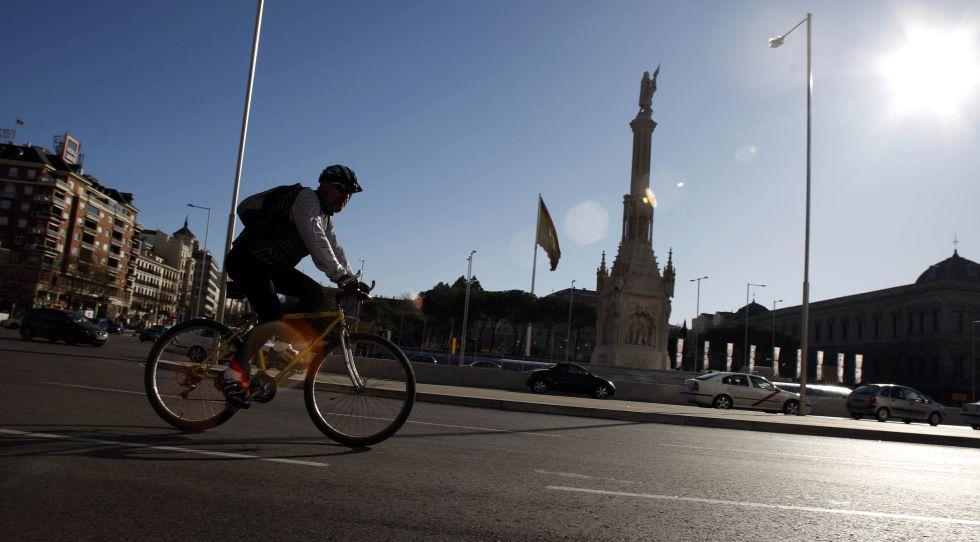 Un ciclista circula frente al monumento a Colón en el Paseo de Recoletos de Madrid.