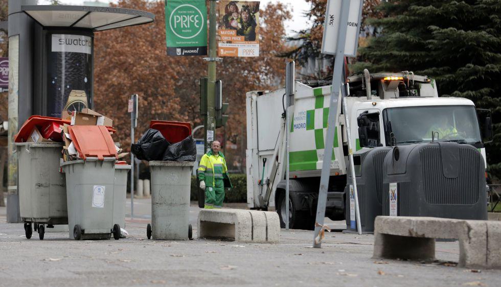 Un trabajador municipal junto a cubos de basura rebosantes  en otoño de 2013.