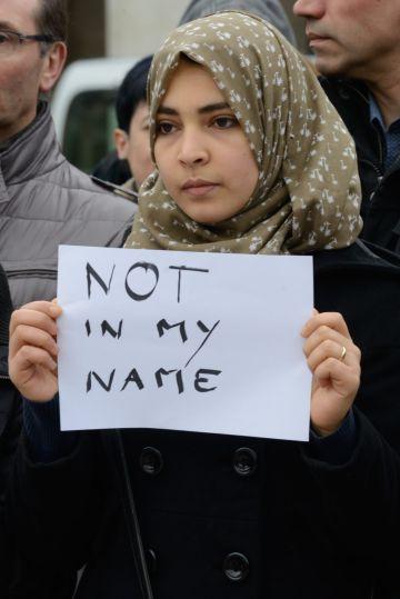 Una joven musulmán muestra un cartel con el mensaje 'No en mi nombre' en la concentración celebrada en Vitoria contra los atentados de Bruselas.