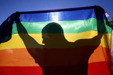 Figura de Sergio proyectada sobre una bandera arcoíris.