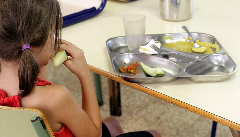 Una niña almuerza en un comedor escolar