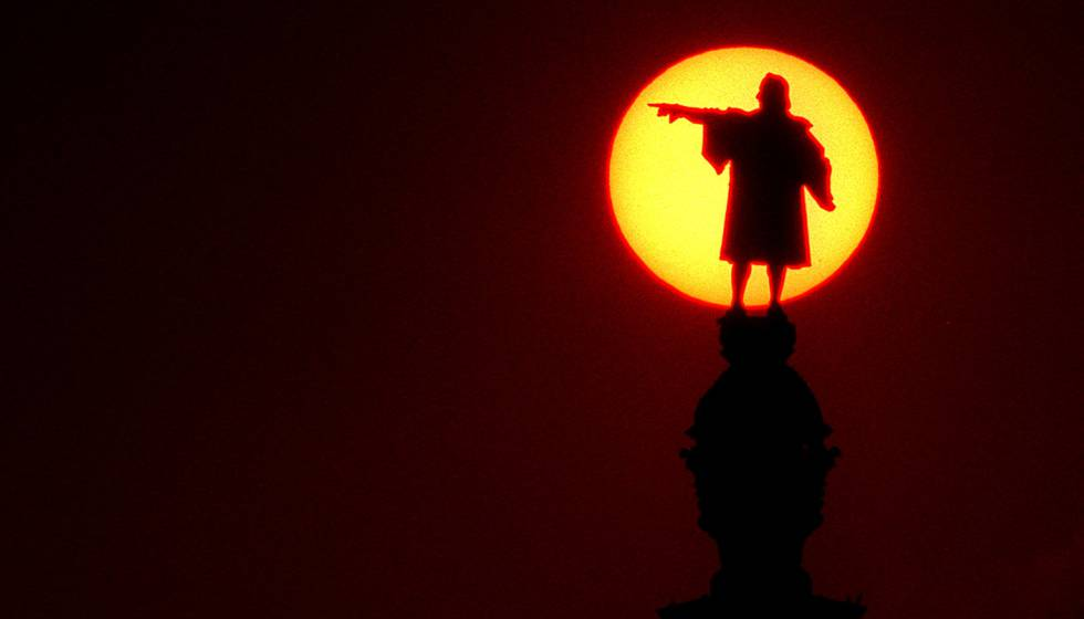 La escultura de Colón del monumento barcelonés rodeado del sol.